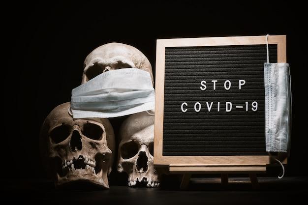 レターボードの近くにマスクを付けた人間の頭蓋骨stopcovid19