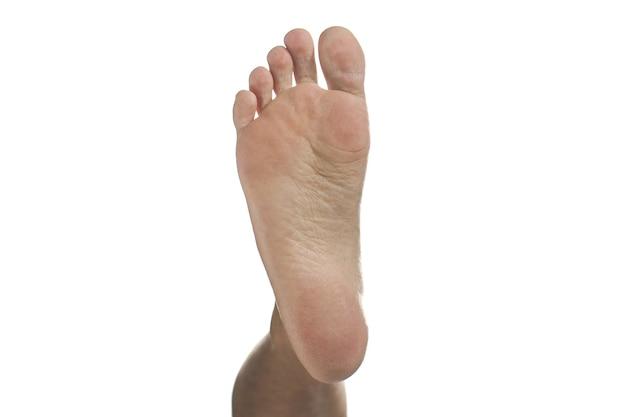 白で隔離される足の人間の足の裏。