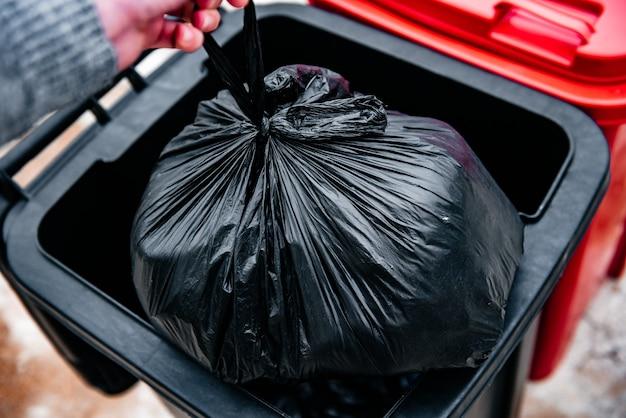 Человек, выбрасывающий мусор в черные мусорные баки.