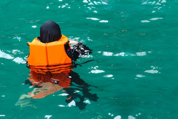 Human wearing life jacket and floating on blue sea water.