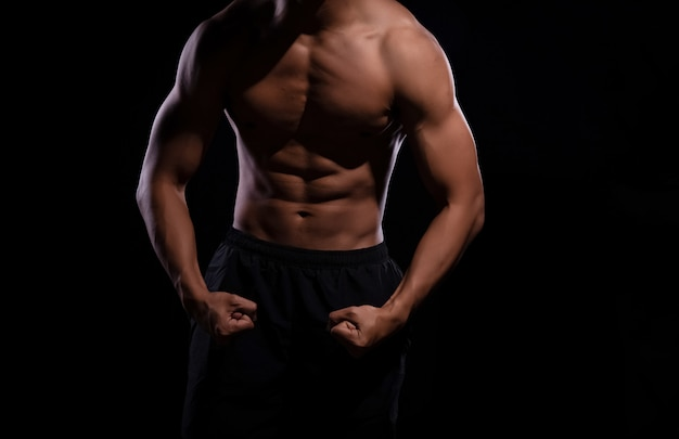 The human with muscular torso on black background, show fit and firm body, strong muscle