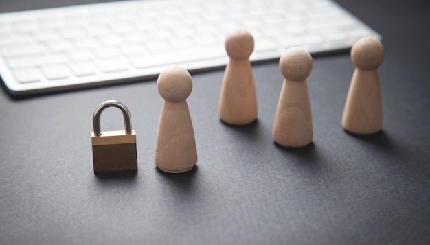 Human wooden figures with a padlock and computer keyboard.