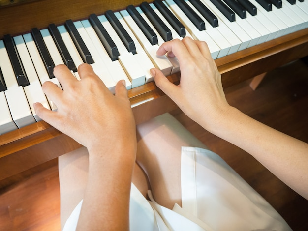 The humand hand is pressing on piano keys