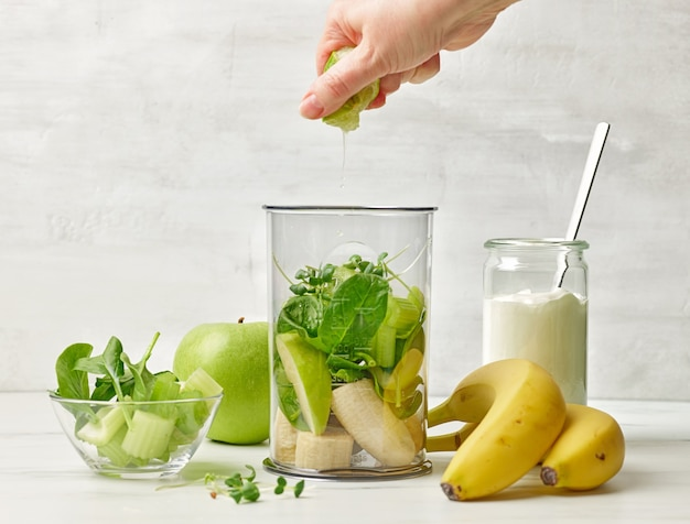 Humane hand squeezing lime juice into blender container for making healthy breakfast smoothie on kitchen table, selective focus