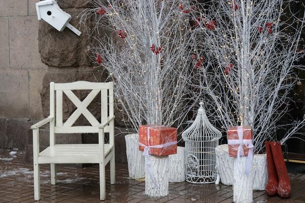 흰색 나무와 선물 상자 근처의 겸손한 흰색 산타 의자. 휴일 새를 위한 새장