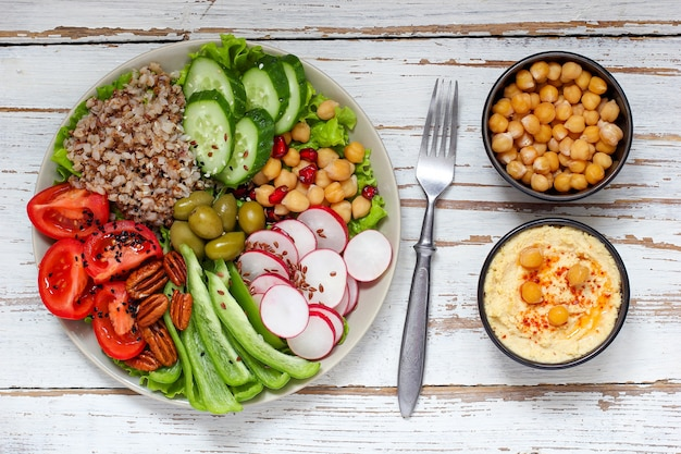 Hummus in bowl, vegetables sticks, chickpeas, olives.