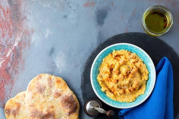 Хумус, нут, со специями и лавашем, лепешка в тарелке на поверхности серого камня