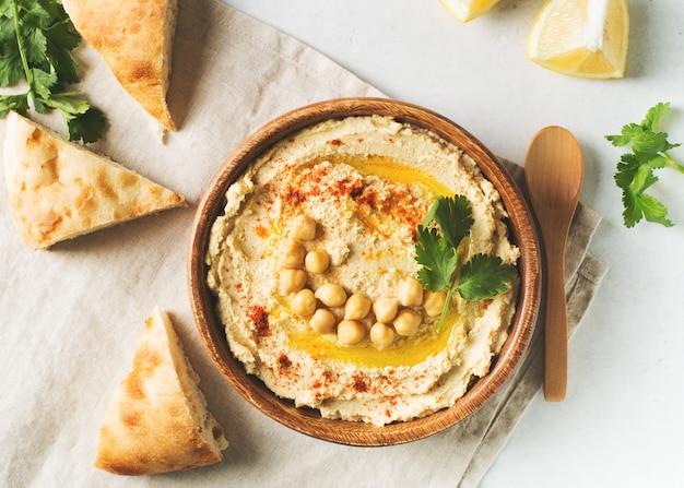 Окунь хумус с нута, лаваш и петрушка в деревянной тарелке на белом фоне