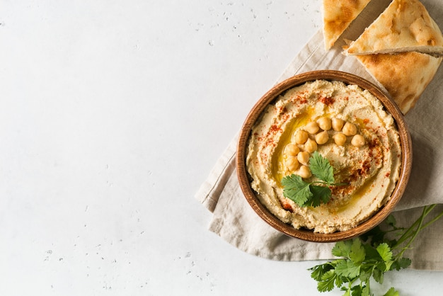 Hummus dip with chickpea, pita  and parsley in wooden plate on white background