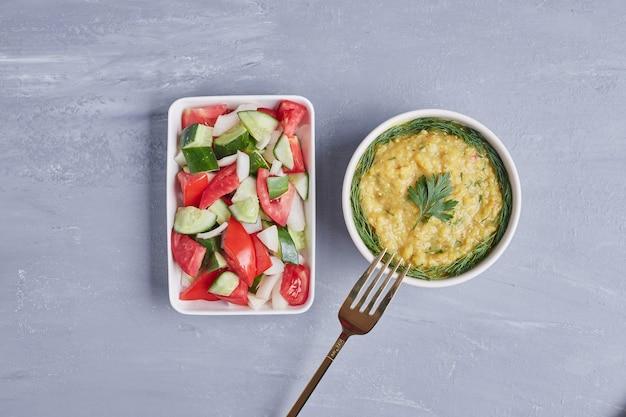 Хумус в белой чашке с зеленью и овощным салатом.