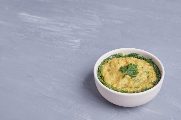 Хумус в белой чашке с травами, угол обзора.