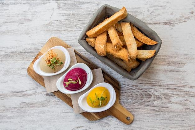 Хумус трио видно сверху, свекла с трюфелем, морковь с карри и традиционные.