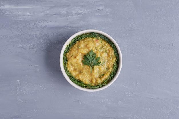 Hummus in una tazza bianca con erbe aromatiche al centro.