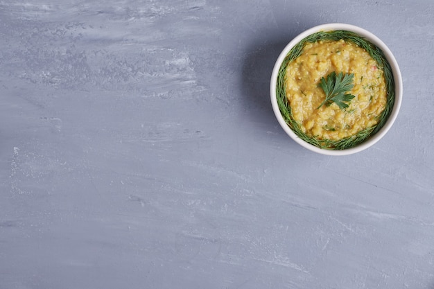 Hummus in una tazza bianca con erbe aromatiche.
