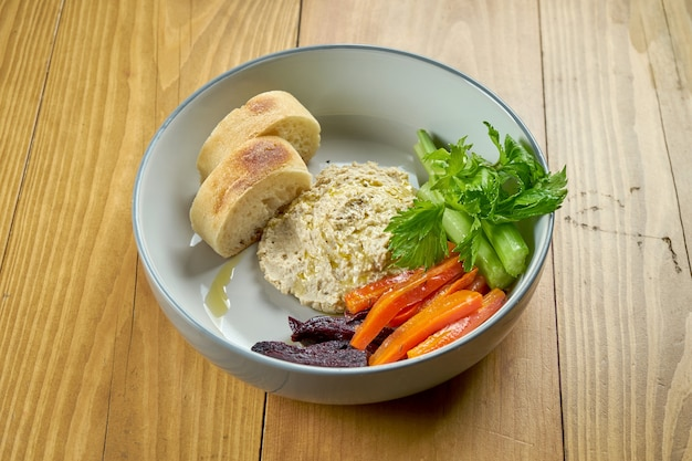 Hummus with baked vegetables and baguette in a bowl on a wooden background. vegetarian dish. israeli cuisine