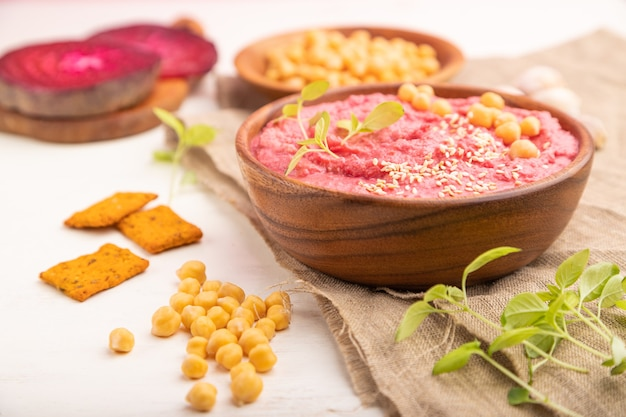 Hummus with beet and microgreen basil sprouts in wooden bowl on a white wooden surface and linen textile