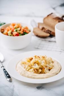 콜리 플라워, 토마토 및 오이 샐러드, 빵 및 커피를 곁들인 후 머스. 중동 요리