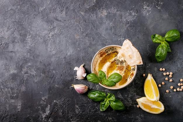 セラミックボウルにオリーブオイル、ピタパン、クミンを挽いたフムスを、暗いテクスチャーの表面にレモン、バジル、ひよこ豆を添えて。上面図、フラットレイ