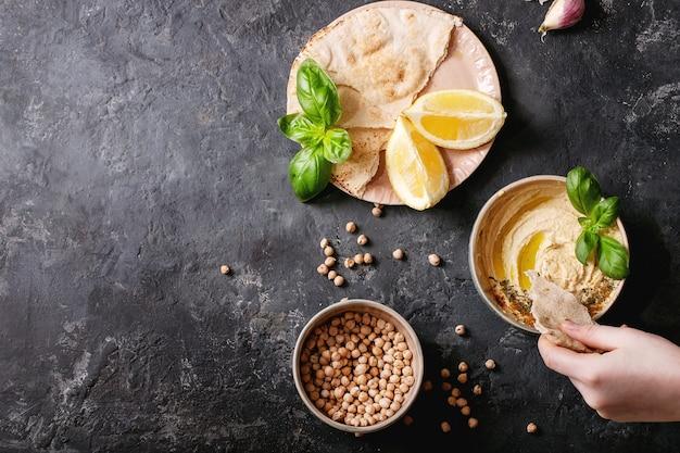 올리브 오일, 피타 빵 및 세라믹 그릇에 빻은 커민을 곁들인 후 머스는 어두운 질감 표면 위에 레몬, 바질, 병아리 콩과 함께 제공됩니다. 평면도, 평면 위치