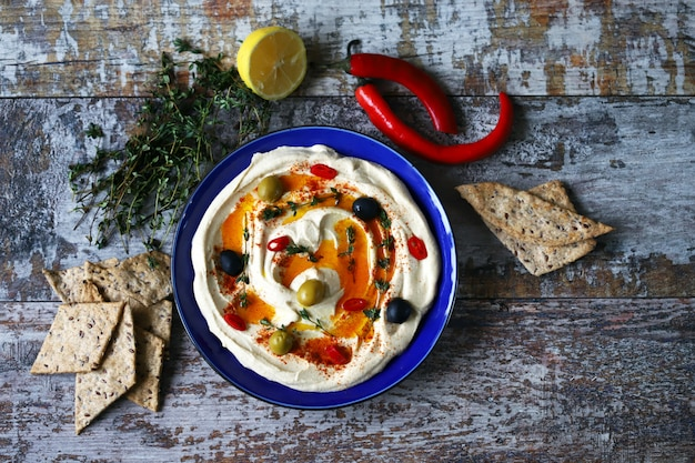 Хумус с оливками, паприкой и оливковым маслом на тарелке. синяя тарелка с хумусом.