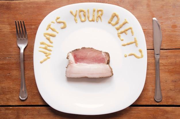 흰 접시에 겨자 소스로 쓴 유머 질문과 생 돼지 고기의 두꺼운 조각