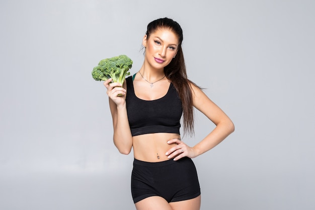 Humorous nutrition concept: slim, healthy and fit young woman with broccoli isolated