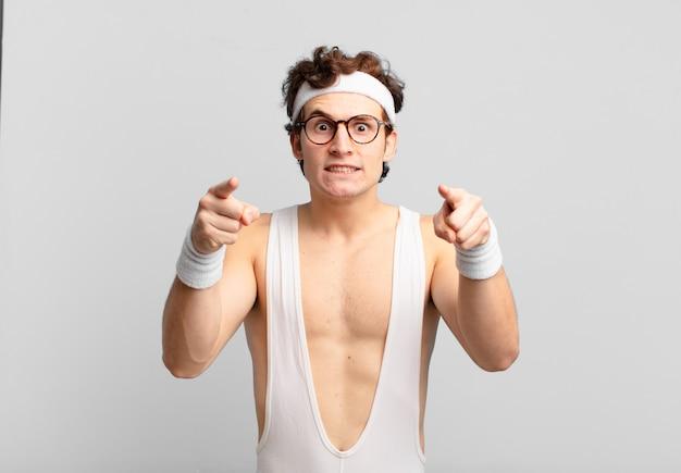 두 손가락과 화난 표정으로 정면을 가리키는 유머러스 한 스포츠 남자, 의무를 다하라고 말합니다.