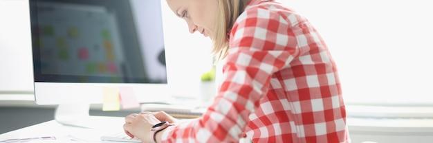 테이블에 컴퓨터 키보드에 입력하는 굽은 여자. 척추의 곡률 잘못된 자세 개념