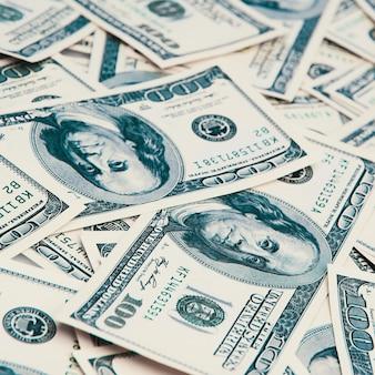 A hundred american banknotes are scattered. cash hundred-dollar bills, dollar background image.