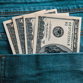 A hundred american bills in cash in the back pocket of his jeans
