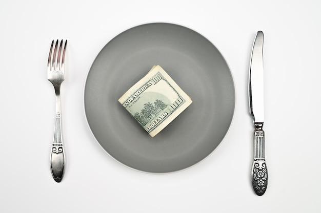 孤立した白い背景の上のフォークとナイフで、プレート上の百ドル札。高品質の写真