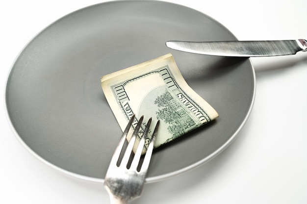 Hundred dollar bill on plate, with fork and knife on isolated white background . high quality photo