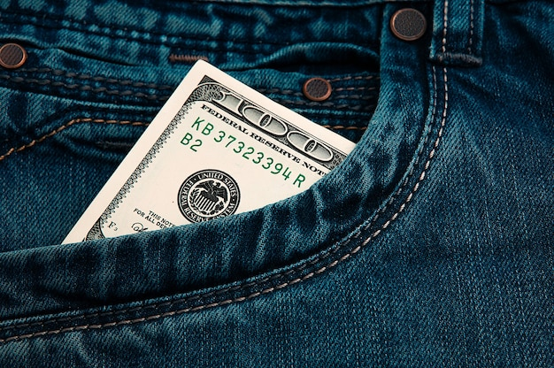 A hundred-dollar bill in the pocket of his jeans. the one hundred american dollar bill is sticking out. one bill is us dollars. color style.