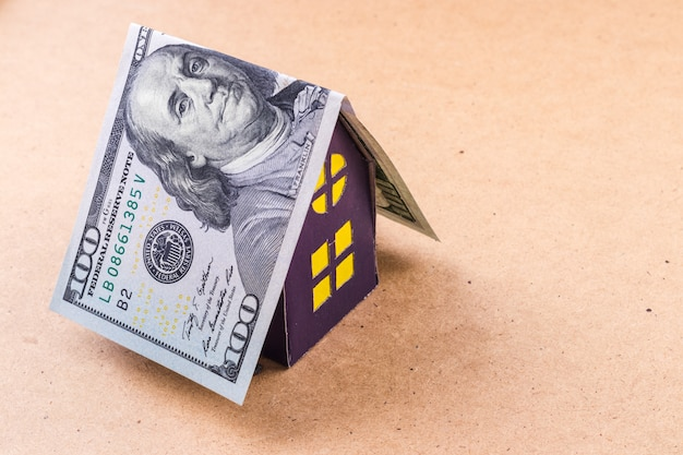 Hundred dollar bill roof covers purple cardboard house.