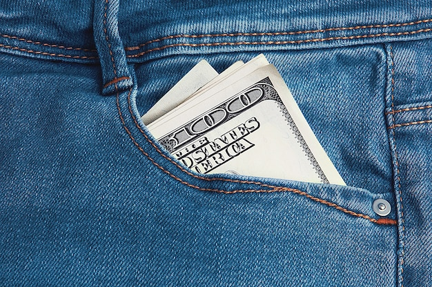 Hundred-dollar bills are folded in half in the back pocket of his blue jeans.