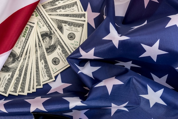 Hundred dollar bills are located on the american flag .