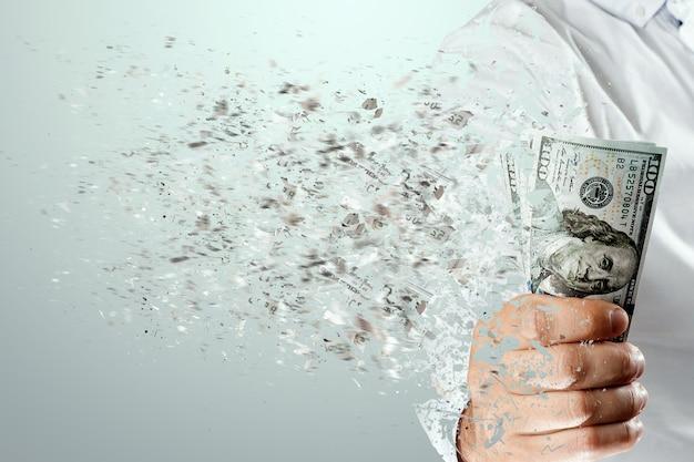 Купюры в сто долларов разлетаются в прах в руке человека. потеря денег, большие расходы, кредиты, ипотека.
