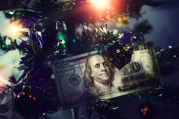 100달러 지폐입니다. 크리스마스 트리에 돈입니다. 파란색 배경에 작은 장식된 크리스마스 트리.