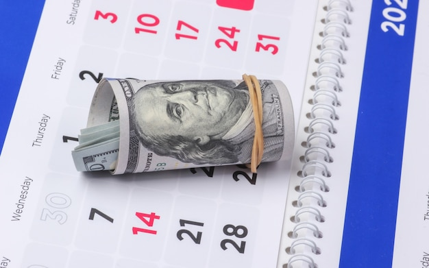 カレンダーの百ドル札。ショッピング時間、レンタル料金。ビジネスと金融