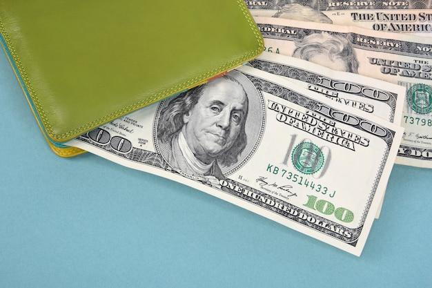 Стодолларовые купюры выглядывают из зеленого кожаного кошелька на бирюзовом фоне.
