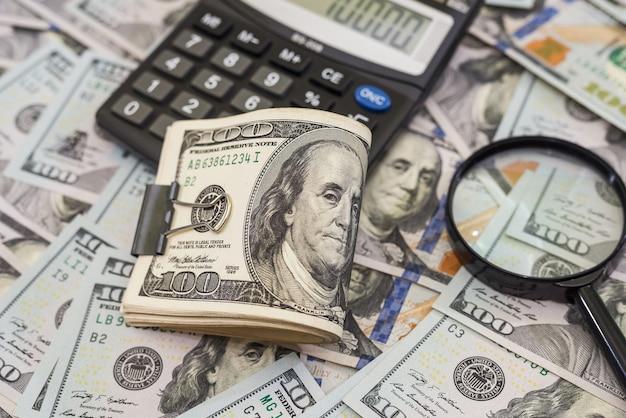 Стодолларовые купюры с лупой и калькулятором на деньги. вид сверху. много долларов.