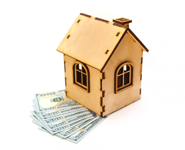 Hundred-dollar bills and wooden toy house isolated on white