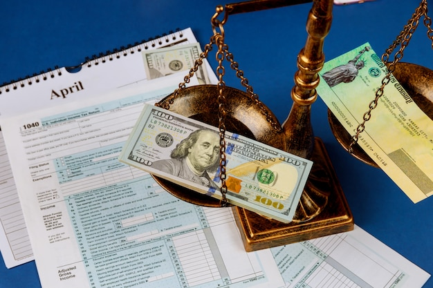 Hundred us dollar bills on a table scales of justice and gavel irs form.