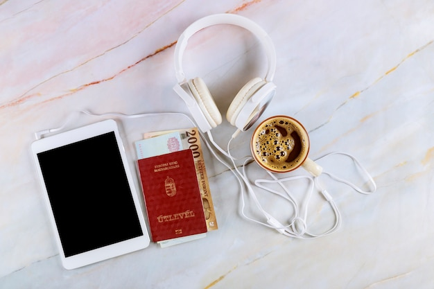 The hungarian citizenship passports, overhead cup of black espresso coffee, tablet and headphone