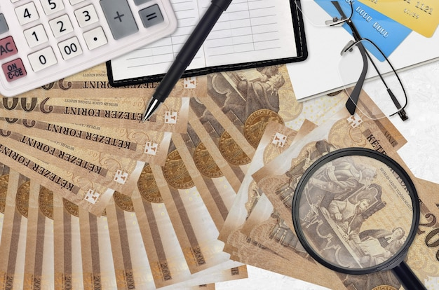 Купюры венгерского форинта и калькулятор с очками и ручкой