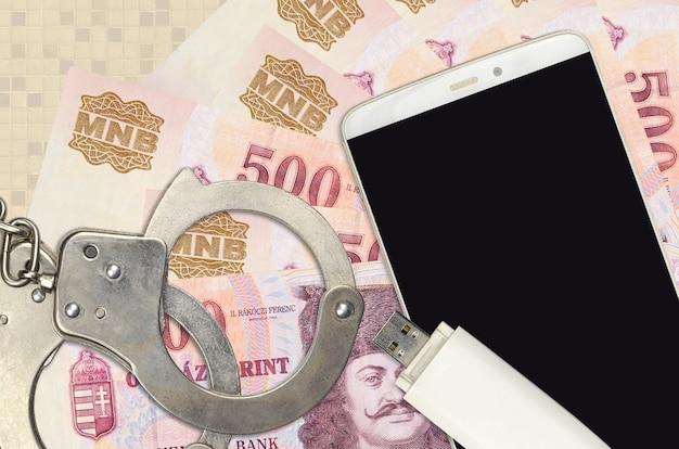 Купюры венгерского форинта и смартфон с полицейскими наручниками