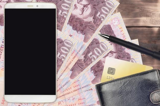 Купюры венгерского форинта и смартфон с кошельком и кредитной картой