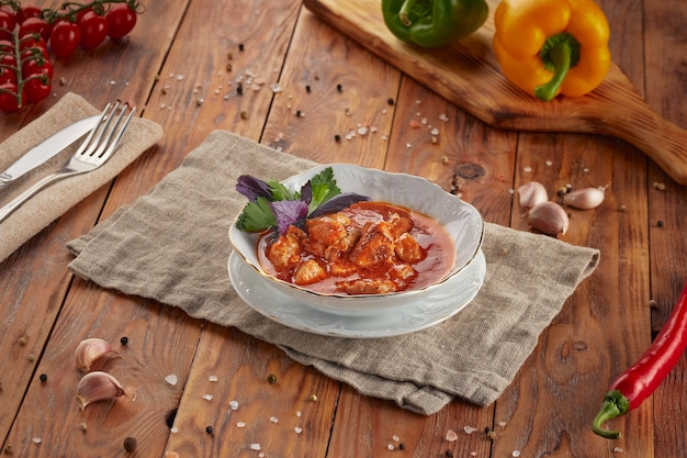 Hungarian goulash soup bograch, wooden background