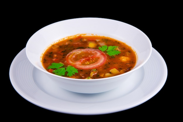 Hungarian goulash - thick vegetable soup with beef and tomatoes on white boul.