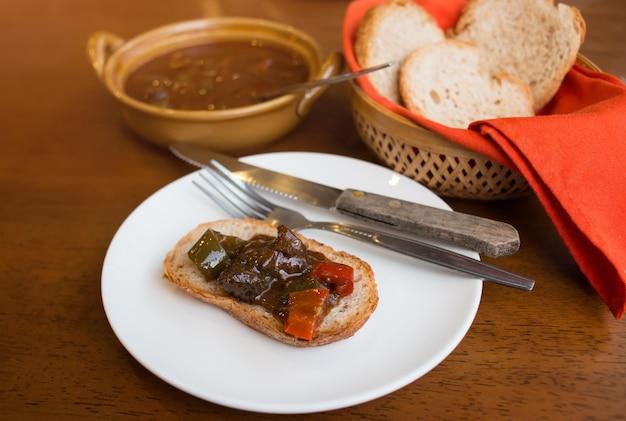 フルフレーバーのビーフシチューの濃い色のパンとハンガリーのグーラッシュをお召し上がりいただけます。